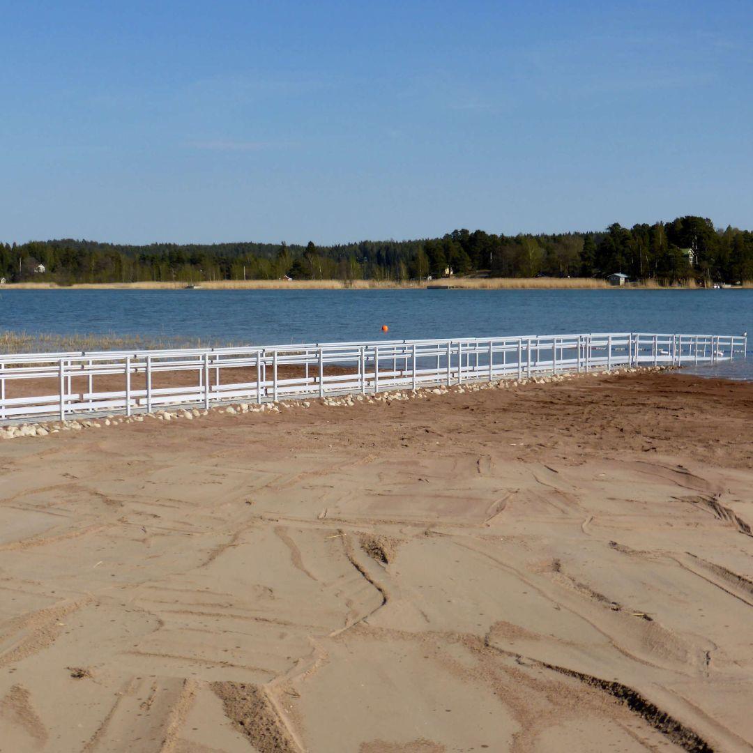 Pitkä KahlausLaituri hiekkarannalla, valmis, merivesi alhaalla.